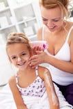 Karosseriensorgfalt - Frau und kleines Mädchen, die Sahne auftragen Stockbild
