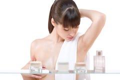 Karosseriensorgfalt: Junge Frau, die Lotion im Badezimmer anwendet lizenzfreie stockfotos