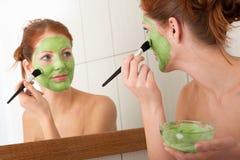 Karosseriensorgfaltserie - Frau, die Gesichtsschablone anwendet Stockfoto