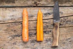 Karotte ganz und Schnitt zur Hälfte mit Messer auf hölzernem Hintergrund Lizenzfreie Stockfotos