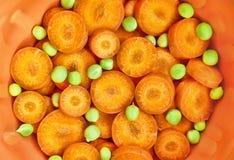 Karotte und grüne Erbsen in der Keramik Lizenzfreie Stockbilder