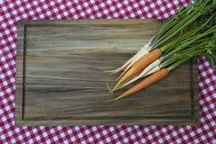 Karotte und Petersilie auf hölzernem Brett Stockfotografie