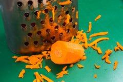 Karotte und zerriebene Karotte auf einem Schneidebrett stockfotografie