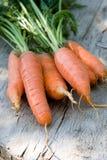 Karotten über der alten gealterten hölzernen Tabelle im Garten lizenzfreie stockfotos