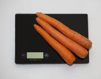 Karotten auf einer digitalen weißen Küchenskala Lizenzfreies Stockfoto