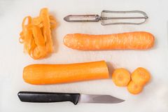 Karotten, ein Messer und ein Gemüseschäler auf einem weißen hackenden Brett Stockfotos