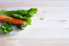 Karotten, Kopfsalat, Petersilie auf einem hölzernen Hintergrund Stockfotos