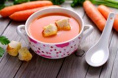 Karottensuppe in einer Porzellanschüssel Stockfoto