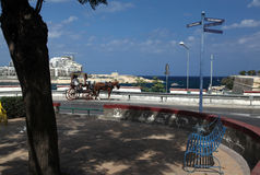 Karozzin and Fort Tigne. A Karozzin waits for fares from tourists in Valletta overlooking Sliema and Fort Tigne Royalty Free Stock Photo