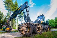 Karpacz, Poland - August 17/2017; Forest cutting. Timber harvester. Forest cutting with the help of a harvester. Worker servicing the machine after harvest Stock Images