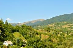 Βουνά, που καλύπτονται από τα δέντρα, και μικρά σπίτια. Στοκ Εικόνα