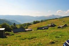 Βουνά, ξύλινα σπίτια, ευχάριστος μπλε ουρανός πρωινού. Στοκ εικόνα με δικαίωμα ελεύθερης χρήσης