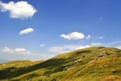 Βουνά, στον ευχάριστο μπλε ουρανό, που καλύπτεται από τη χλόη. Στοκ φωτογραφία με δικαίωμα ελεύθερης χρήσης
