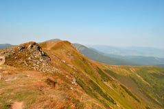 Βουνά, στον ευχάριστο μπλε ουρανό. Στοκ Φωτογραφία