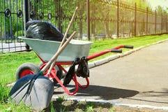 Karretje met huisvuil en hulpmiddelen om in openlucht schoon te maken Tegen achtergrond van groen gras royalty-vrije stock afbeeldingen