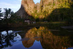 Karst rock wall in Ramang-ramang. Karst rock wall reflecting on the water in ramang-ramang tourist destination in Maros, South Sulawesi, Indonesia Royalty Free Stock Images