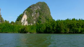 Karst rocks rise above the water surface. Picturesque seascapes with mangrove forests under the blua tropical sky of the province PhangNga in Southern Thailand stock video footage