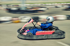 Kart racer speed. A man is driving Go-kart with speed in the park on karting track - front view Royalty Free Stock Images