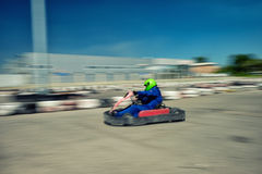 Kart racer speed. A man is driving Go-kart with speed in the park on karting track - front view Stock Photo