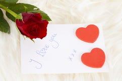 Karta, czerwieni róża i serca, Obrazy Royalty Free