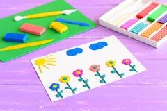 Karta z plasteliną kwitnie, słońce i chmury Plastelina ustawiająca na drewnianym stole Dziecko modelarskiej gliny sztuka Wykonuje obrazy royalty free