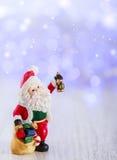 Karte der frohen Weihnachten mit Santa Claus-Figürchen Beleuchtet Hintergrund mit Raum für Text Der Junge gelegt auf den Schnee Stockfotos