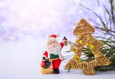 Karte der frohen Weihnachten mit Santa Claus-Figürchen Beleuchtet Hintergrund mit Raum für Text Der Junge gelegt auf den Schnee W Stockbild