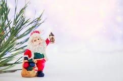 Karte der frohen Weihnachten mit Santa Claus-Figürchen Beleuchtet Hintergrund mit Raum für Text Der Junge gelegt auf den Schnee W Lizenzfreie Stockbilder