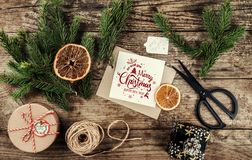 Karte der frohen Weihnachten mit Tannenzweigen, Geschenken auf hölzernem Hintergrund mit Scheren und Strang des Jutefasers Weihna stockbilder