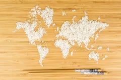 Karte der Welt gemacht vom weißen Reis mit zwei Bambusstöcken Lizenzfreies Stockfoto