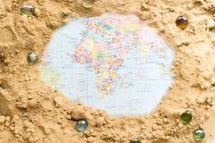 Karte der Welt unter dem Sand Seeshell mit Ozean auf Hintergrund Stockfotos