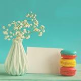Karte des leeren Papiers mit Tasse Tee andvase in der Blume und in den Makronen für Frauentag Lizenzfreie Stockbilder