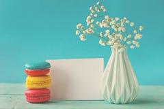 Karte des leeren Papiers mit Tasse Tee andvase in der Blume und in den Makronen für Frauentag Stockbilder