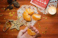 Karte des neuen Jahres mit Kerzen und Mandarine Stockbild