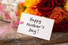 Karte mit ` glücklichem Mutter ` s Tag-` Text-Geschenk und Rosen Lizenzfreie Stockfotos