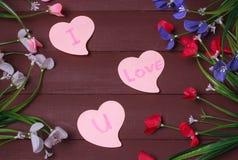 Karte mit Mitteilungs-Liebe Sie auf dem Buchstaben auf hölzernem Hintergrund Stockfoto