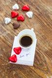 Karte mit Mitteilungs-Liebe Sie, Tasse Kaffee und Praline Stockfotos