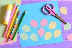 Karte mit Papierluftballonen, Scheren, Kleberstock, farbiges Papier, zeichnet auf einer Tabelle an Unterrichtend scherzt, um Sche Stockfoto