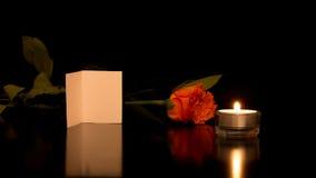Karte mit Rose und Kerze auf glänzender schwarzer Oberfläche Lizenzfreies Stockfoto