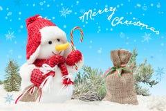 Karte mit Schneemann im roten Hut und im Schal, mit Geschenk ` s Säcken Feiertagskonzept für Weihnachten und neue Jahre mit Aufsc Lizenzfreie Stockbilder