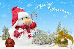 Karte mit Schneemann im roten Hut und im Schal nahe Tannenbällen auf blauem Hintergrund und fallenden Schneeflocken Lizenzfreies Stockfoto