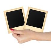 Karte mit zwei alte Fotopapieren in der Frauenhand lokalisiert auf Weiß Lizenzfreie Stockfotografie