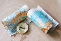 Karte und Kompass, die auf dem hölzernen Hintergrund liegen lizenzfreie stockbilder