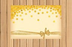 Karte verziert mit goldenem Bogen und Sternen auf hölzernem Lizenzfreie Stockbilder