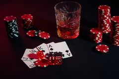 Karten des Pokerspielers Sind auf dem Tisch Chips und ein Glas des Cocktails mit Whisky Kombination von Karten - Royal Flush Stockfoto