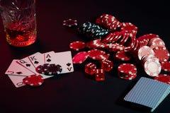 Karten des Pokerspielers Sind auf dem Tisch Chips und ein Glas des Cocktails mit Whisky Kombination von Karten - Royal Flush Stockfotografie