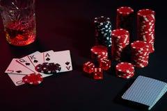Karten des Pokerspielers Sind auf dem Tisch Chips und ein Glas des Cocktails mit Whisky Kombination von Karten - Royal Flush Lizenzfreies Stockbild