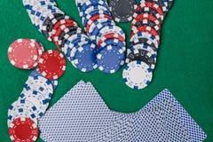 Karten und Pokerchips mit Rot würfelt auf einer grünen Pokertabelle Stockfotografie