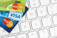 Karten-Visum und MasterCard werden auf weißen Tastaturhintergrund gesetzt Stockfoto