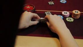 Kartenkombination, -as und -könig der Pokerspielervertretung gute auf Schürhakentabelle Nahaufnahme des Mannes Hand Kasinoglückss stock footage